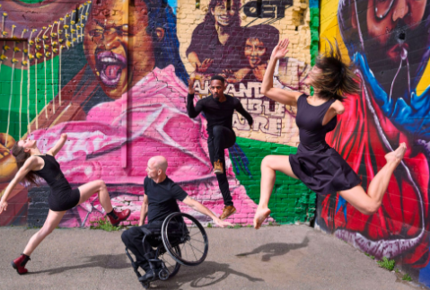 Four dancers in black clothes with colorful graffiti background